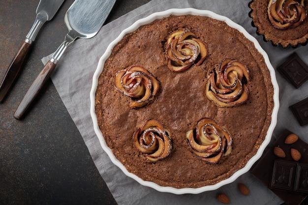 Bolo de chocolate caseiro com frangipane e flores de maçã em uma superfície de concreto escuro
