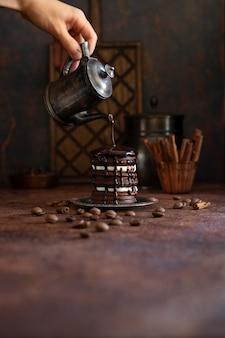 Bolo de chocolate caseiro com gotas de chocolate líquidas. mão feminina derrama chocolate do pote de café