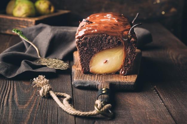 Bolo de chocolate caseiro com pêra em superfície de madeira rústica. brownie com calda de chocolate.