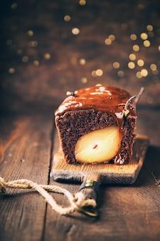 Bolo de chocolate caseiro com pêra na superfície de madeira rústica com bokeh. brownie de natal com calda de chocolate. foco seletivo.