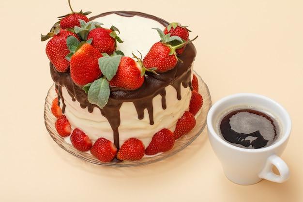 Bolo de chocolate caseiro decorado com morangos frescos e folhas de hortelã em um prato de vidro e uma xícara de café no fundo bege