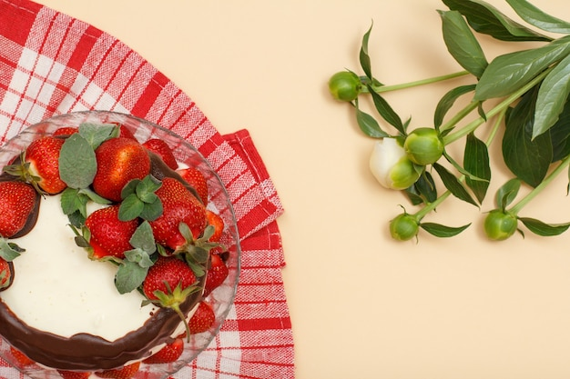 Bolo de chocolate caseiro decorado com morangos frescos e folhas de hortelã na placa de vidro com guardanapo de cozinha e buquê de peônias sobre fundo de cor bege. vista do topo