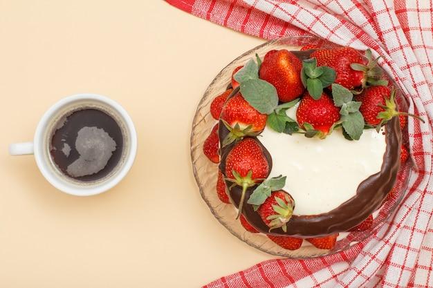 Bolo de chocolate caseiro decorado com morangos frescos e folhas de hortelã na placa de vidro com guardanapo de cozinha e xícara de café sobre fundo de cor bege. vista do topo