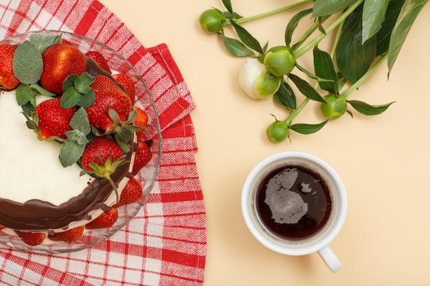 Bolo de chocolate caseiro decorado com morangos frescos e folhas de hortelã na placa de vidro com guardanapo de cozinha, xícara de café e buquê de peônias sobre fundo de cor bege. vista do topo