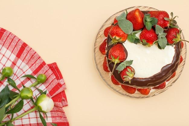 Bolo de chocolate caseiro decorado com morangos frescos e folhas de hortelã na placa de vidro e guardanapo de cozinha com buquê de peônias sobre fundo de cor bege. vista do topo