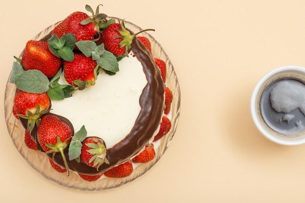 Bolo de chocolate caseiro decorado com morangos frescos e folhas de hortelã na placa de vidro e xícara de café sobre fundo de cor bege. vista do topo