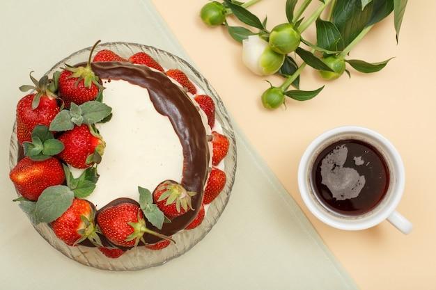 Bolo de chocolate caseiro decorado com morangos frescos e folhas de hortelã na placa de vidro, xícara de café e buquê de peônias em fundo de cor cinza e bege. vista do topo
