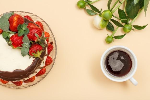 Bolo de chocolate caseiro decorado com morangos frescos e folhas de hortelã na placa de vidro, xícara de café e buquê de peônias sobre fundo de cor bege. vista do topo