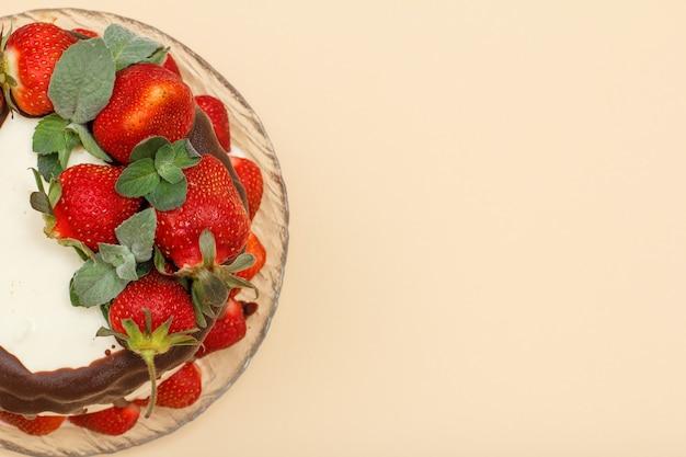 Bolo de chocolate caseiro decorado com morangos frescos em placa de vidro e fundo de cor bege. vista superior com espaço de cópia