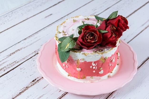 Bolo de chocolate coberto com creme de manteiga de merengue suíço, com flores vermelhas para decorar.