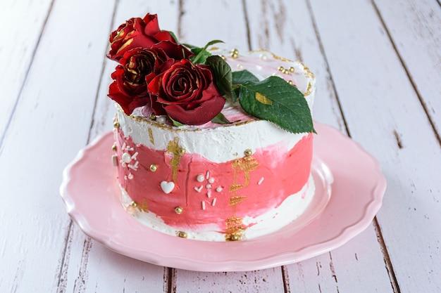 Bolo de chocolate coberto com creme de manteiga de merengue suíço, com três flores vermelhas no topo. em um prato rosa.