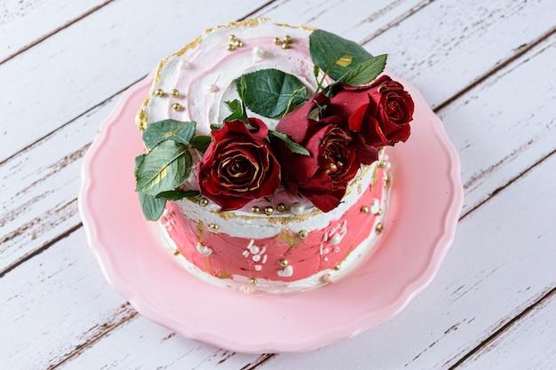 Bolo de chocolate coberto com creme de manteiga de merengue suíço, com três flores vermelhas no topo.