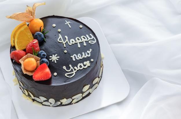 Bolo de chocolate coberto com laranja, morango, mirtilo e cape gooseberry em um pano branco, espaço de cópia e conceito de sobremesa