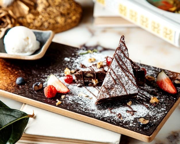 Bolo de chocolate com açúcar em pó servido com frutas e sorvete