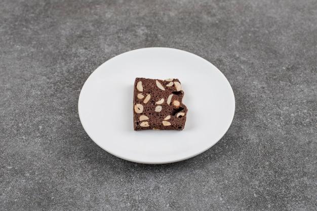 Bolo de chocolate com amendoim. fatia de bolo em prato branco sobre superfície cinza
