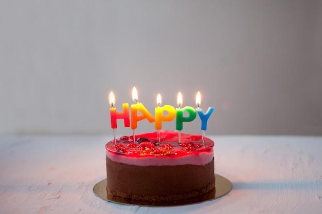 Bolo de chocolate com arco-íris, saudações de aniversário feliz em fundo branco