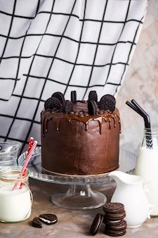 Bolo de chocolate com biscoitos em um carrinho de vidro entre os vasos com leite