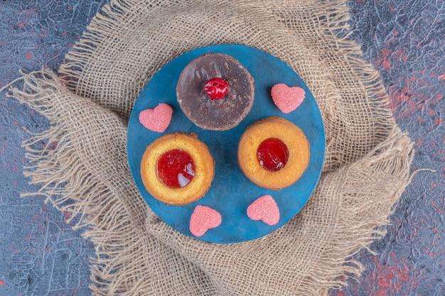 Bolo de chocolate com bolos recheados de geleia e marmeladas em um quadro azul na mesa abstrata.