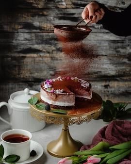 Bolo de chocolate com cacau em pó em cima da mesa