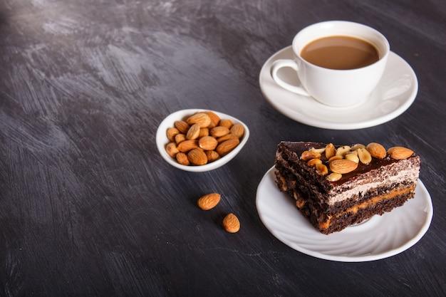 Bolo de chocolate com caramelo, amendoim e amêndoas em um fundo preto de madeira.