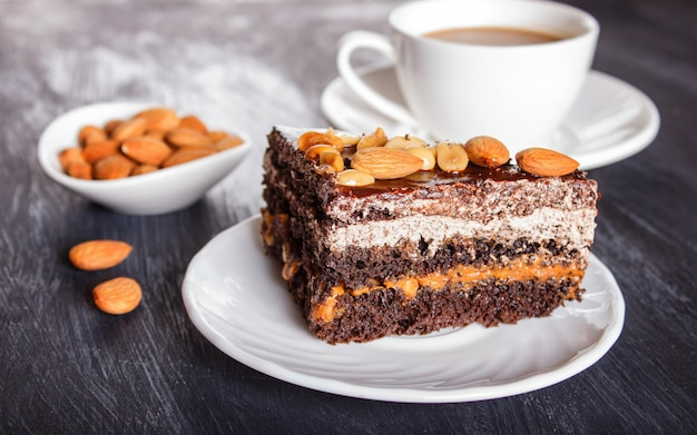 Bolo de chocolate com caramelo, amendoim e amêndoas em uma superfície de madeira preta.