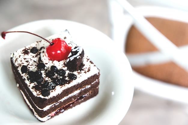Bolo de chocolate com cerejas vermelhas sobre um fundo branco.