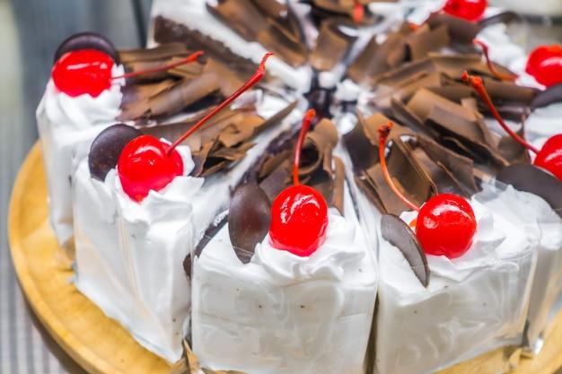 Bolo de chocolate com cerejas vermelhas.