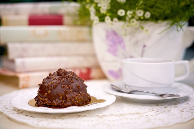 Bolo de chocolate com chá na mesa com flores e livros.