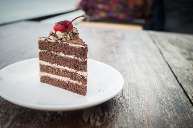 Bolo de chocolate com cobertura de cereja no acolhedor café ao ar livre