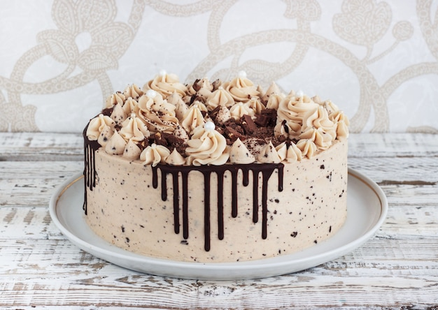 Bolo de chocolate com cobertura de creme de mousse em fundo de madeira branco grunge