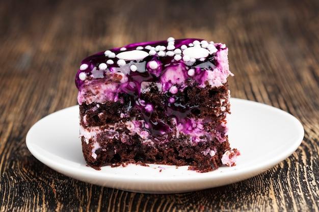 Bolo de chocolate com creme coberto com geleia roxa de frutas vermelhas, bolo de várias camadas feito de bolos com creme de queijo cottage e sabor de frutas vermelhas