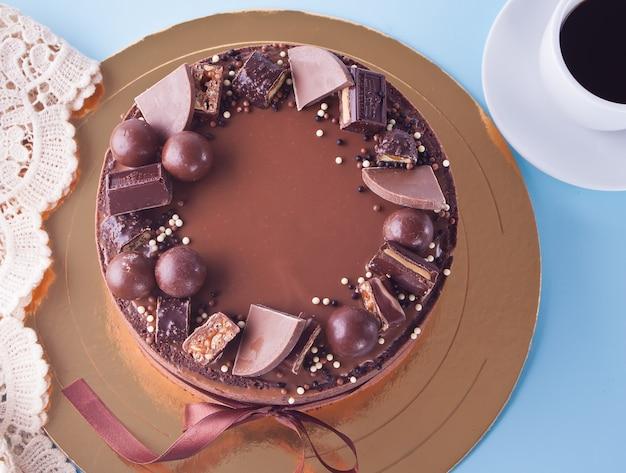 Bolo de chocolate com doces e fita em uma mesa azul