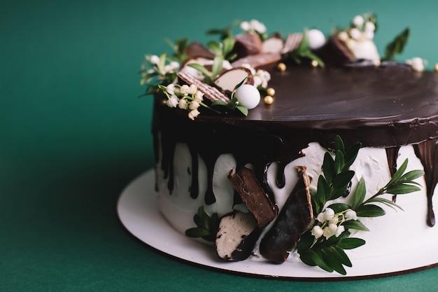 Bolo de chocolate com doces e flores sobre fundo verde, close-up