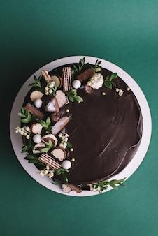 Bolo de chocolate com doces e flores sobre fundo verde, vista superior