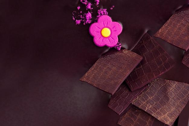 Bolo de chocolate com enfeites de chocolate branco e rosa de maçapão violeta. decoração de bolo de chocolate com martzipã e flor doce vista de cima