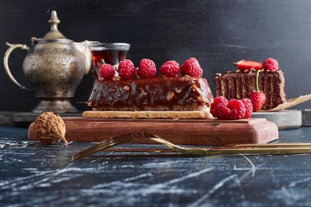 Bolo de chocolate com framboesas em uma placa de madeira.