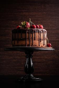 Bolo de chocolate com frutas, morangos e cerejas. bolo em um fundo marrom escuro. copie o espaço