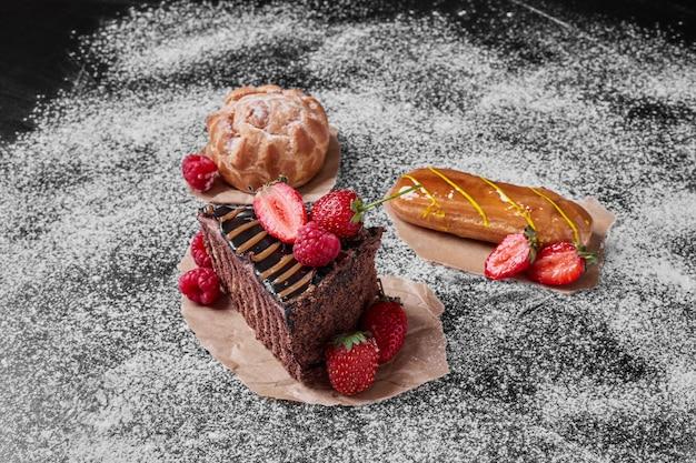 Bolo de chocolate com frutas no preto.