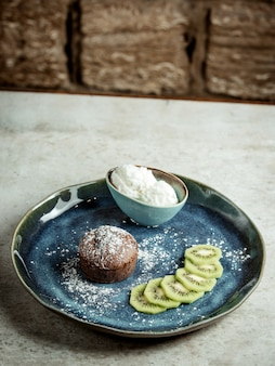 Bolo de chocolate com kiwi fatiado e sorvete