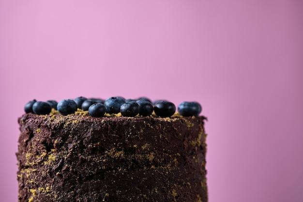 Bolo de chocolate com mirtilos com pistache à terra e frutas vermelhas em um fundo amarelo.
