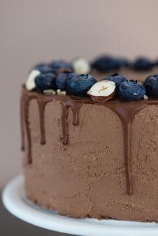 Bolo de chocolate com mirtilos e nozes em um fundo marrom