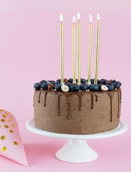 Bolo de chocolate com mirtilos nozes e velas em um prato alto branco sobre um fundo rosa