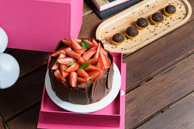 Bolo de chocolate com morangos e folhas de manjericão para decorar (vista de cima). em caixa de presente rosa, ao lado de balões e brigadeiros (com espaço para texto).