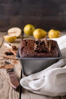 Bolo de chocolate com peras e canela em fundo de madeira velho.