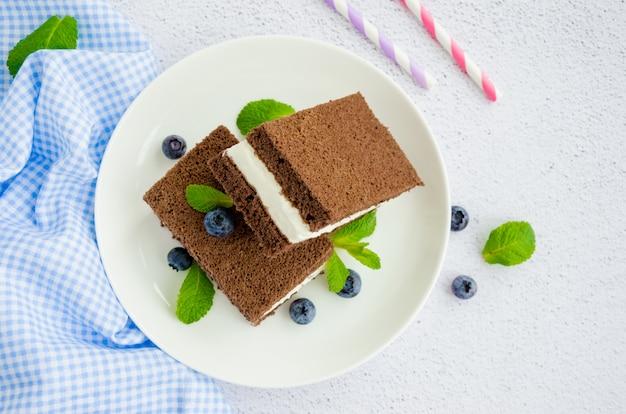 Bolo de chocolate com recheio de creme de leite em um prato branco com mirtilos frescos e folhas de hortelã com duas garrafas de leite e tubos.