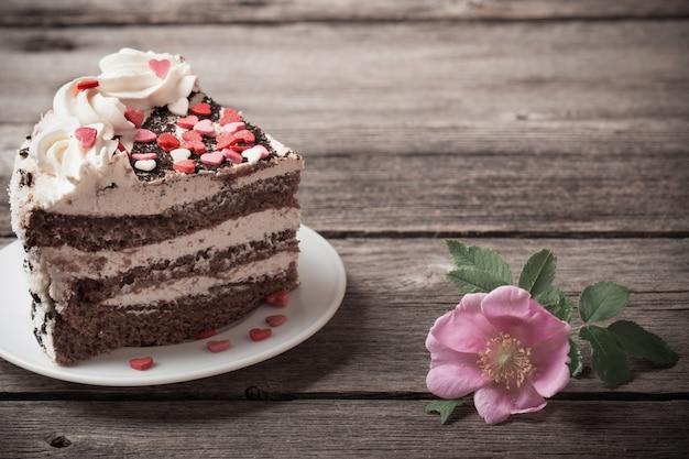 Bolo de chocolate com rosa em fundo de madeira velho