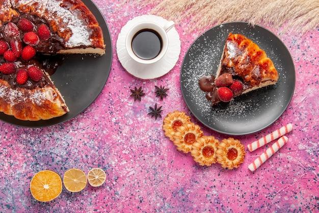 Bolo de chocolate de morango com biscoitos e chá na mesa rosa, vista de cima