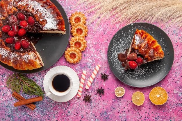 Bolo de chocolate de morango com vista superior e uma xícara de chá na superfície rosa