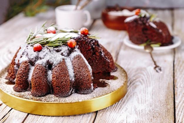 Bolo de chocolate de natal decorado com frutas e alecrim em uma mesa de madeira branca