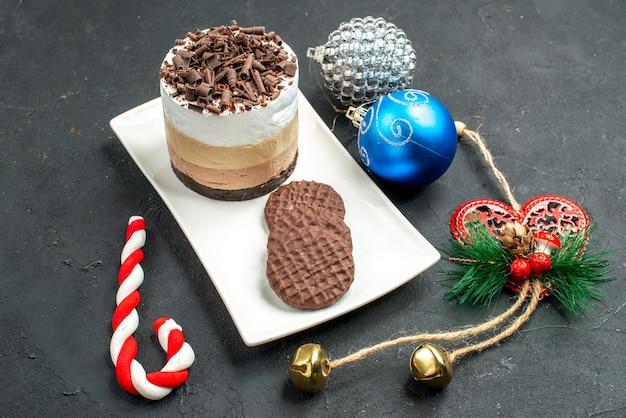 Bolo de chocolate de vista frontal e biscoitos em uma placa retangular branca brinquedos de árvore de natal em fundo escuro isolado
